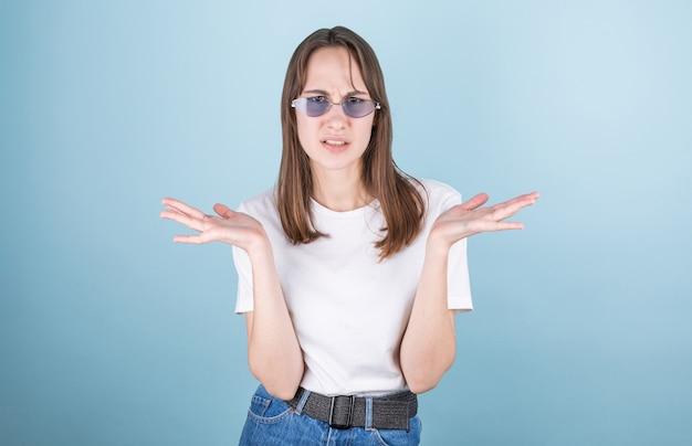 Een jong meisje met uitgestrekte armen dat haar schouders ophaalt, zegt: ik weet het niet. geïsoleerd op een lichtblauwe muur. Premium Foto