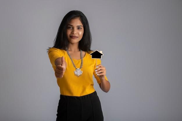 Een jong meisje of zakenvrouw met een klein uitgesneden bord en poseren op een grijze muur.