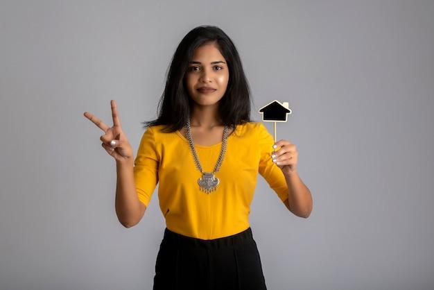 Een jong meisje of zakenvrouw met een klein uitgesneden bord en poseren op een grijze muur. Premium Foto
