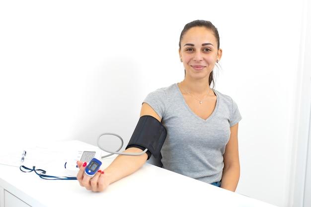 Een jong meisje onderzocht door een arts met aangesloten hartslagsensoren en tonometer