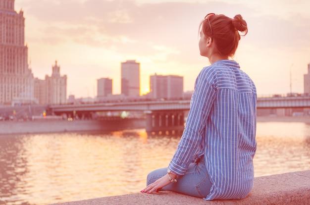 Een jong meisje op de achtergrond van het stadsbeeld kijkt peinzend in de verte.