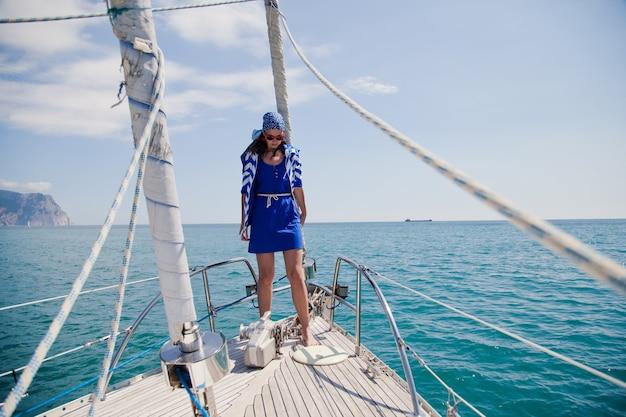 Een jong meisje op de neus van het witte jacht in een nautisch thema. blauw jasje, blauwe sjaal en zonnebril. in de open zee de oceaan