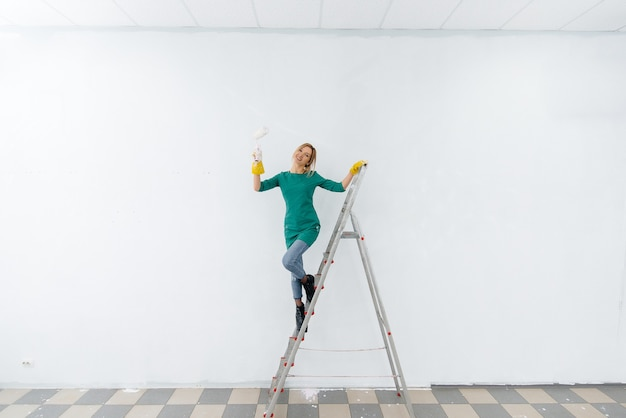 Een jong meisje op een trapladder schildert een witte muur met een roller. reparatie van het interieur.