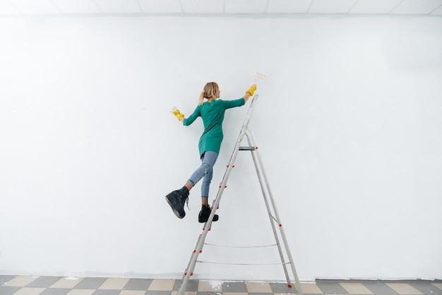 Een jong meisje op een trapladder schildert een witte muur met een roller