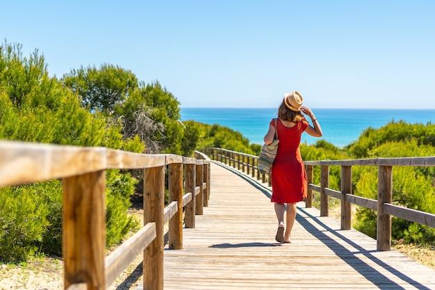Een jong meisje op het houten pad naar playa moncayo in guardamar del segura naast torrevieja, alicante