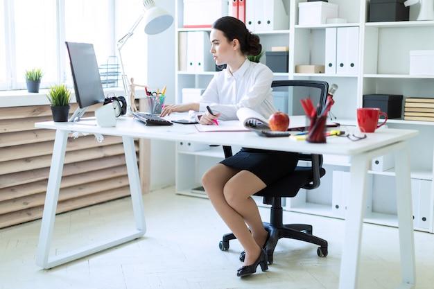 Een jong meisje op kantoor heeft een roze stift in haar hand en werkt met een computer en documenten.