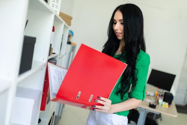 Een jong meisje op kantoor houdt een map met documenten vast.