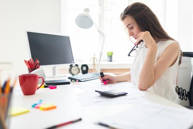 Een jong meisje op kantoor houdt een roze stift, een bril vast en werkt met de documentatie.