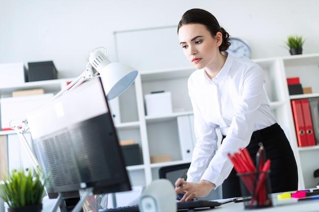 Een jong meisje op kantoor staat bij de tafel, houdt een potlood in haar hand en typt de tekst op de computer.