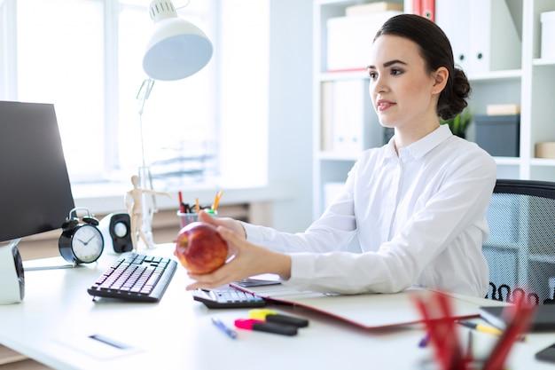 Een jong meisje op kantoor werkt met documenten en strekt een appel uit.