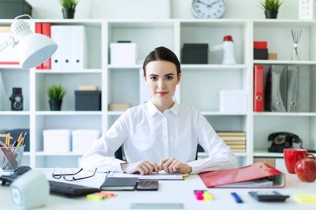 Een jong meisje op kantoor zit aan een tafel en houdt een pen in haar handen.