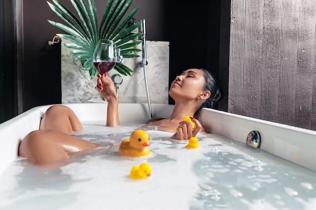 Een jong meisje poseert liggend in een schuimbad, met een bloem en eenden,