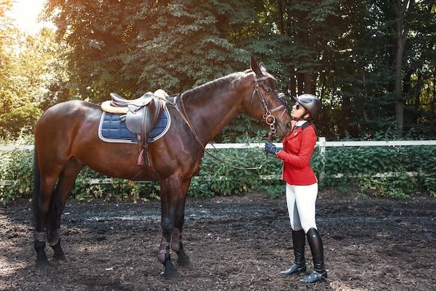 Een jong meisje praat en zorgt voor haar paard. ze houdt van de dieren en brengt haar tijd met plezier door in hun omgeving.