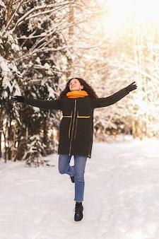 Een jong meisje rent vrolijk door de sneeuw in het winterbos. emoties