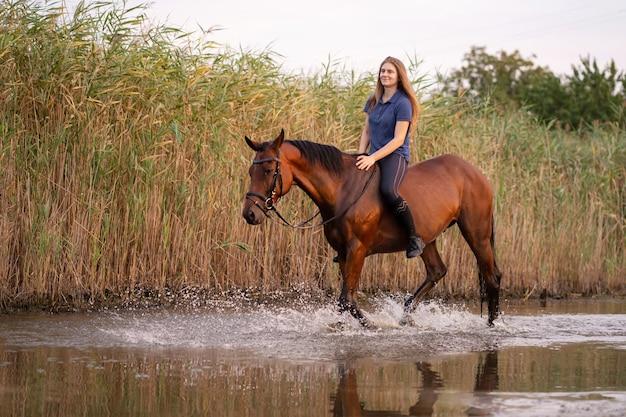 Een jong meisje rijdt op een paard op een ondiep meer. een paard loopt bij zonsondergang op het water