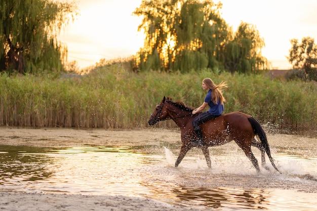 Een jong meisje rijdt op een paard op een ondiep meer. een paard loopt op water bij zonsondergang. zorg en loop met het paard. kracht en schoonheid