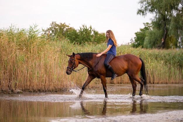 Een jong meisje rijdt op een paard op een ondiep meer.