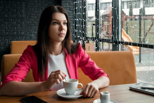 Een jong meisje roert suiker in een kopje koffie, zit in een café achter een houten stolikos