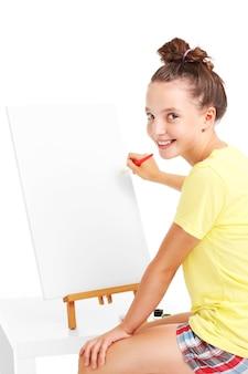 Een jong meisje schilderend op een ezel