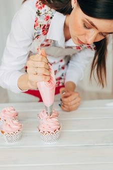 Een jong meisje siert cupcakes met room.