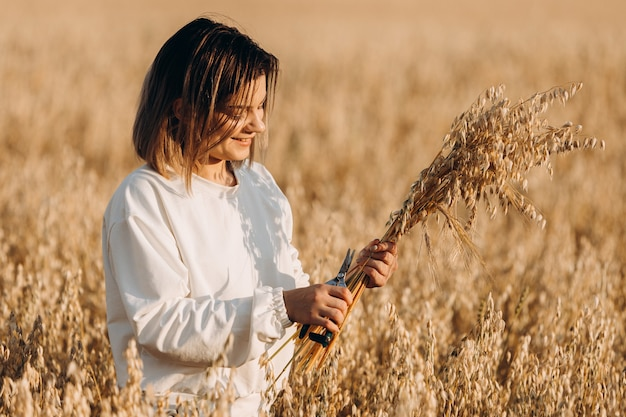 Een jong meisje snijdt de oren van haver met haar handen en glimlacht.