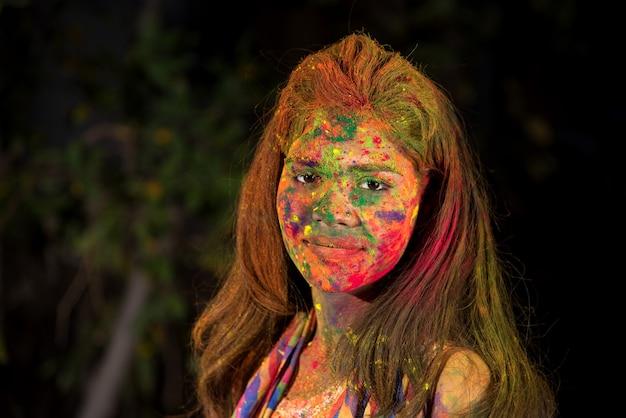 Een jong meisje speelt met kleuren. het concept voor het indiase festival holi. kleuren explosie.