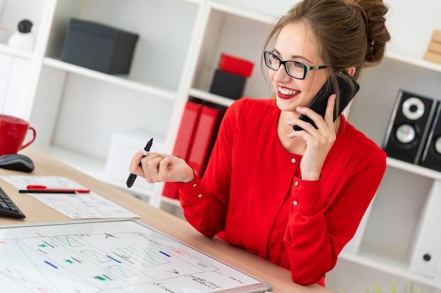 Een jong meisje staat aan een tafel in het kantoor, houdt een zwarte stift in haar hand en praat aan de telefoon.