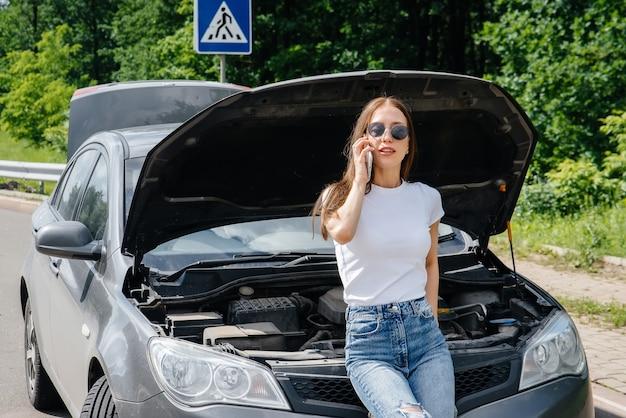 Een jong meisje staat bij een kapotte auto midden op de snelweg en belt om hulp aan de telefoon. storing en pech van de auto. wachten op hulp.