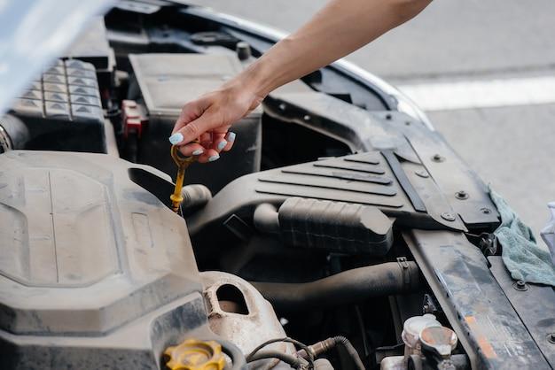 Een jong meisje staat bij een kapotte auto midden op de snelweg en controleert het oliepeil in de motor. storing en pech van de auto. wachten op hulp.