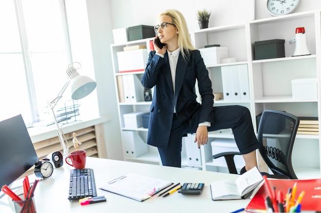 Een jong meisje staat bij een tafel op kantoor, zet haar voet op een stoel en praat aan de telefoon.