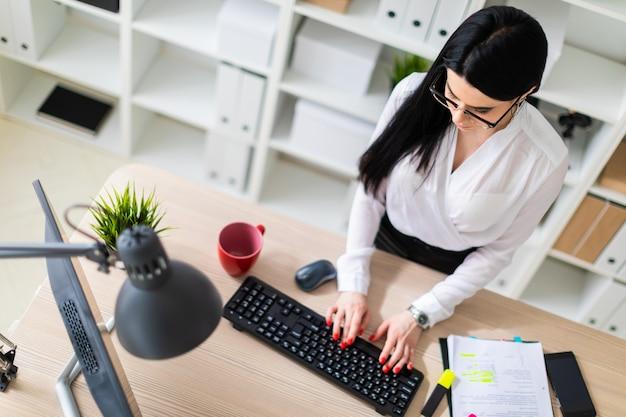 Een jong meisje staat in de buurt van de tafel en typt tekst op het toetsenbord. naast het meisje liggen documenten en een marker.