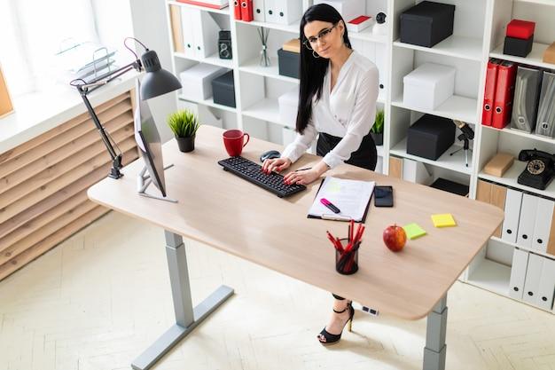Een jong meisje staat in de buurt van de tafel en typt tekst op het toetsenbord.