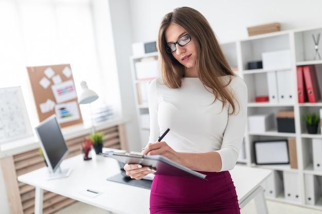 Een jong meisje staat in de buurt van een computer bureau en houdt een tablet met bladen voor records.