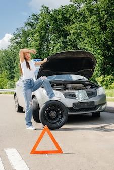 Een jong meisje staat in de buurt van een kapotte auto midden op de snelweg en probeert op een warme zonnige dag een kapot wiel te verwisselen. storing en pech van de auto. wachten op hulp.