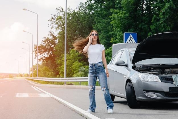 Een jong meisje staat in de buurt van een kapotte auto midden op de snelweg en roept om hulp aan de telefoon, terwijl ze probeert passerende auto's te stoppen. storing en pech van de auto. wachten op hulp.