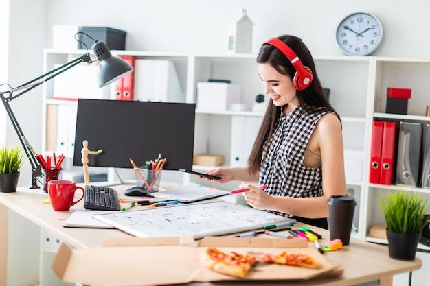 Een jong meisje staat in de buurt van een tafel en houdt een marker en een telefoon in haar handen.