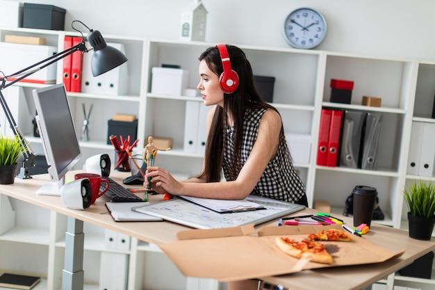 Een jong meisje staat in de buurt van een tafel, houdt een groene marker en kijkt naar de monitor. voor het meisje op tafel ligt een magneetbord. op het hoofd van het meisje dat een koptelefoon draagt.