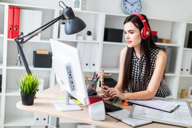 Een jong meisje staat in de buurt van een tafel, houdt een groene marker en kijkt naar de monitor.