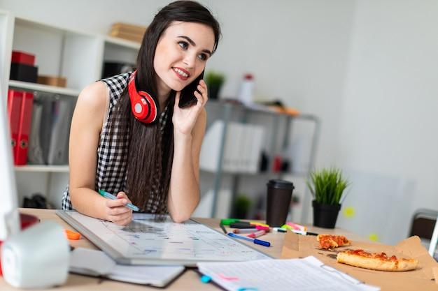 Een jong meisje staat in de buurt van een tafel, houdt een groene marker in haar hand en praat aan de telefoon. in de nek hangt de hoofdtelefoon van het meisje.