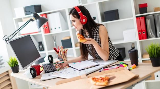 Een jong meisje staat in de buurt van een tafel, met een groene marker en een stuk pizza in haar hand.