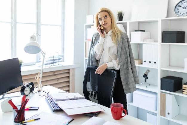 Een jong meisje staat in de buurt van een tafel op kantoor en praat aan de telefoon.