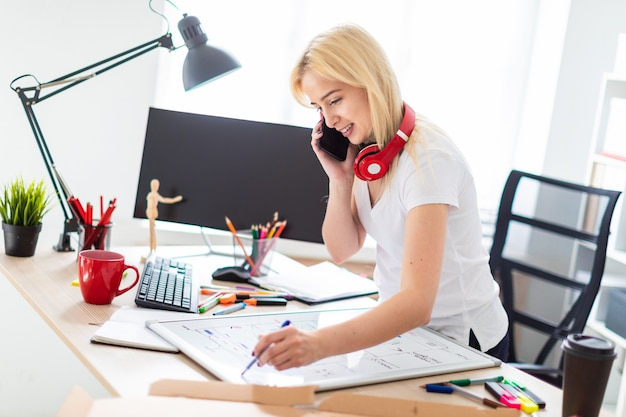 Een jong meisje staat in de buurt van een tafel, praat aan de telefoon en houdt een marker in haar hand. op de tafel ligt een magnetisch bord. in de nek hangt de hoofdtelefoon van het meisje.