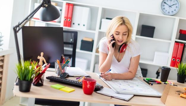Een jong meisje staat in de buurt van een tafel, praat aan de telefoon en houdt een marker in haar hand.