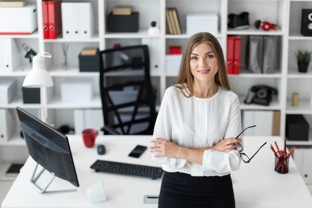 Een jong meisje staat leunend op een tafel in het kantoor en houdt een bril in haar hand.