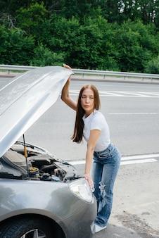 Een jong meisje staat midden op de snelweg bij een kapotte auto en kijkt onder de motorkap. storing en pech van de auto. wachten op hulp.