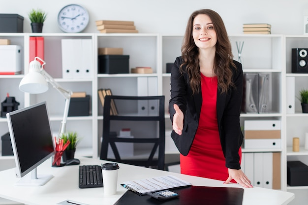Een jong meisje staat op kantoor bij de tafel en strekt haar hand uit