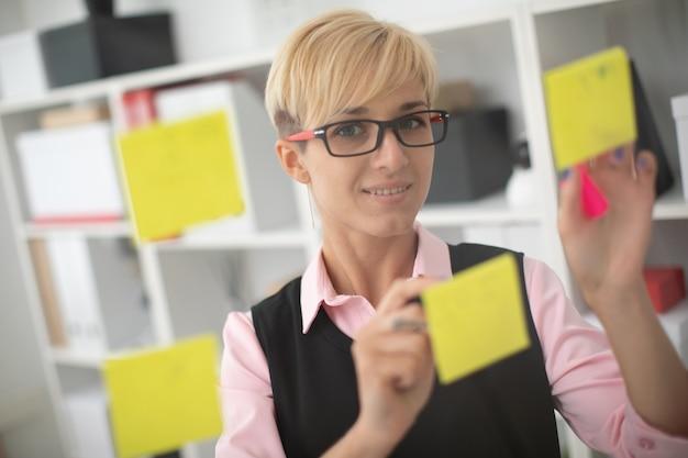 Een jong meisje staat op kantoor bij een transparant bord met stickers.
