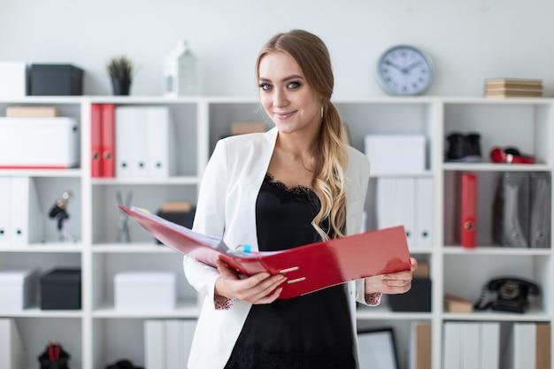 Een jong meisje staat op kantoor naast de plank en heeft een map
