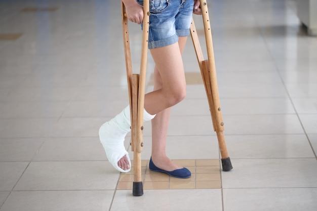 Een jong meisje staat op krukken in de gang van het ziekenhuis.