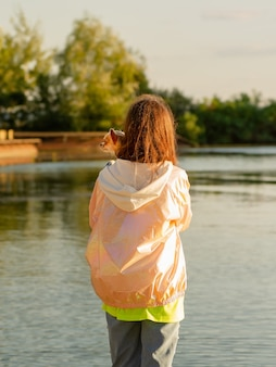 Een jong meisje staat terug naar de camera. meisje bij de rivier met een chihuahua.